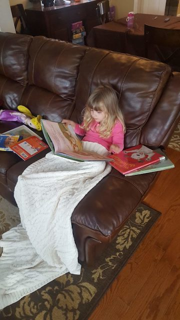 Homeschool toddler reading books by herself