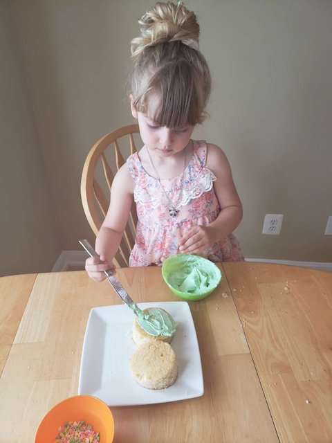 homeschool kid frosting cake for activity