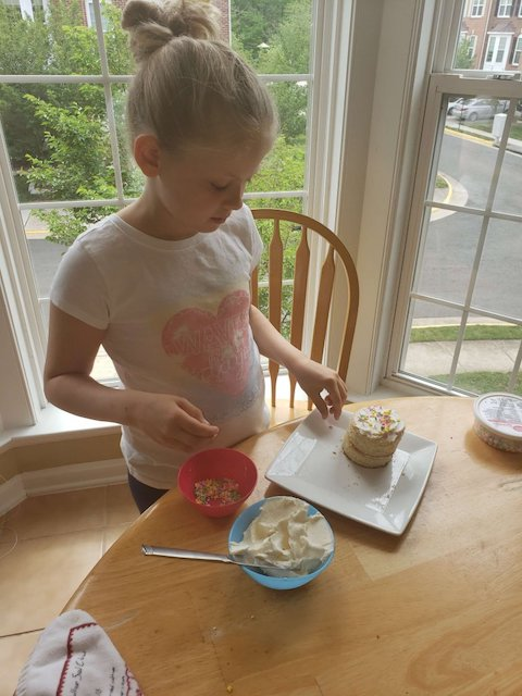 Homeschooler decorating her end of the school year cake activity
