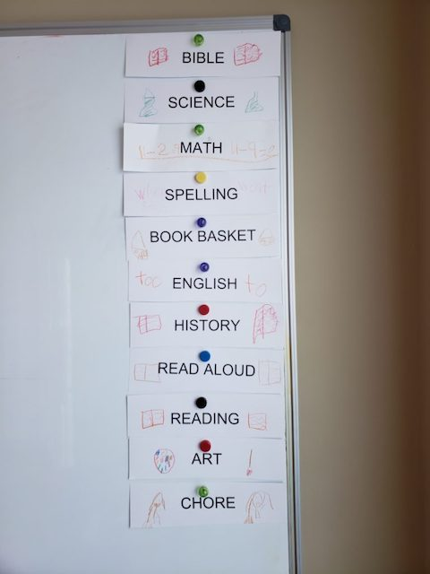 Homeschool Routine cards on a magnetic white board
