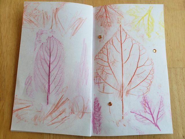 Open fall leaf craft book with many leaf rubs