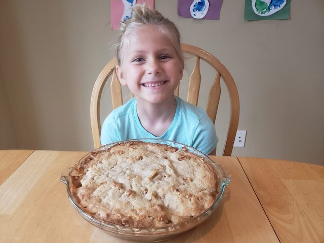 Kindergartener with finshed apple pie for letter of the week