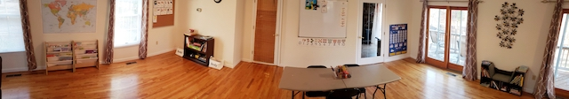 Homeschool Classroom with large shared table (no desks), bookcases, whiteboard
