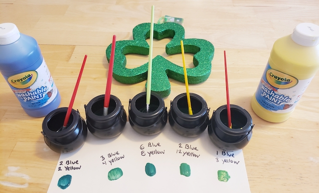 St. Patrick's Day STEM Project showing many different shades of mixed green paint, paint brushes, and a shamrock