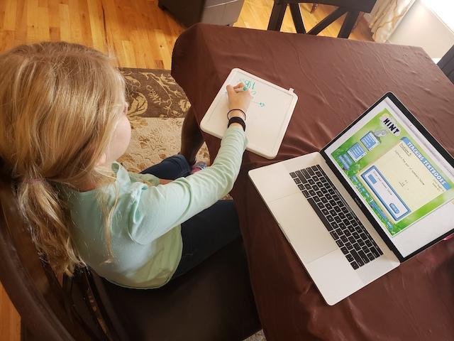 Homeschool Hack: Homeschool kid using mini whiteboard for online math