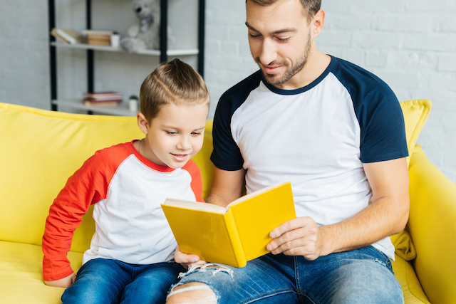 Homeschool kid reading to dad as part of temporary homeschool routine