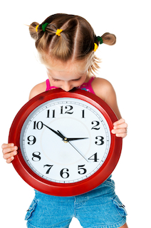 Homeschool kindergarten girl holding a clock and trying to keep to a schedule