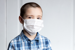 Young kid in face mask for coronavirus response while in public school