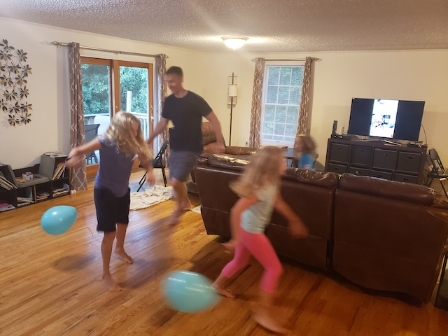 family playing balloon game with virtual recess club